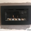 After image of a recently supplied and installed a high efficiency, hole in the wall fire with a black trim and pebbles for Mrs Howarth in Garforth Leeds.